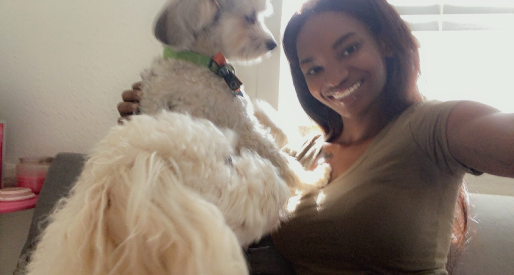 woman taking a selfie with her dog sitting on the couch