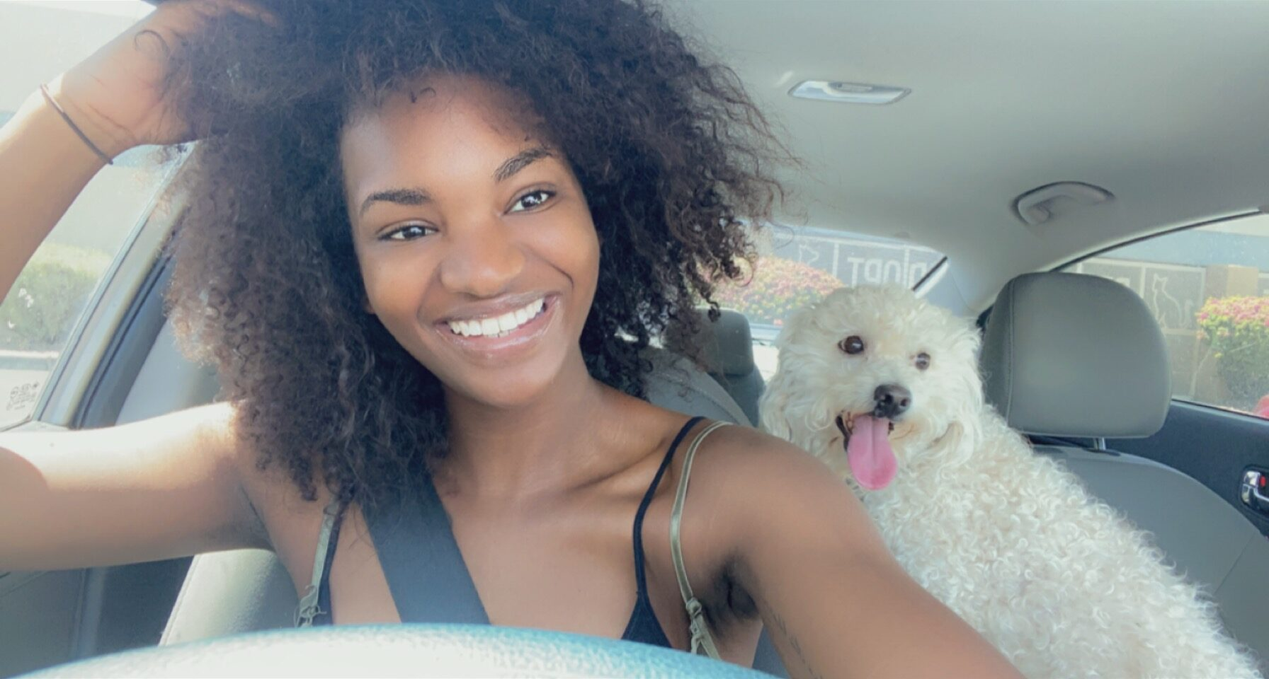 woman taking a selfie in the car with her dog